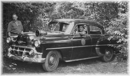 1953 Chevy with Forest Ranger Coral Couchman to the left and District Ranger Vic Schrader in the vehicle - Photo courtesy of the family of Forest Ranger Daniel Showers